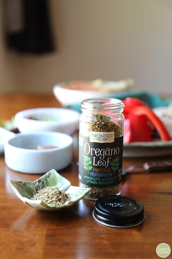 Jar of Frontier Co-op oregano leaf with pizza hummus in background.
