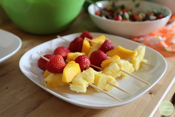 Strawberry & pineapple fruit skewers on plate.