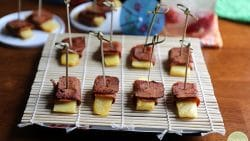 Seitan bacon wrapped pineapple on bamboo covered plate, parasols in background.