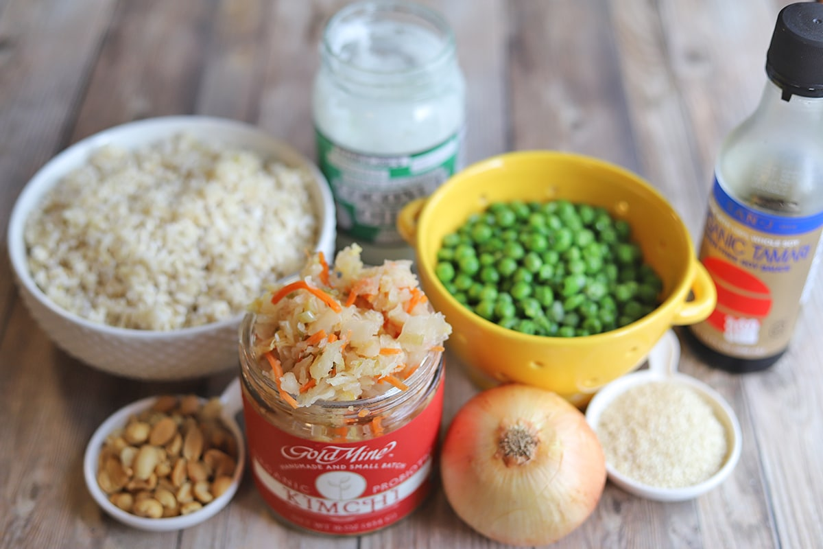 Ingredients for kimchi fried rice: tamari, coconut oil, rice, peanuts, onion, kimchi, and sesame seeds.