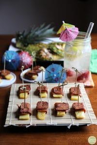 Seitan bacon wrapped pineapple on bamboo covered plate with parasols.