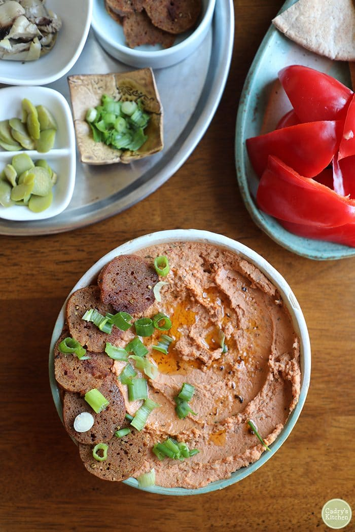 Overhead shot of pizza hummus topped with seitan pepperoni, green onions, and a drizzling of sun-dried tomato oil. On the side, bell pepper wedges for dipping.