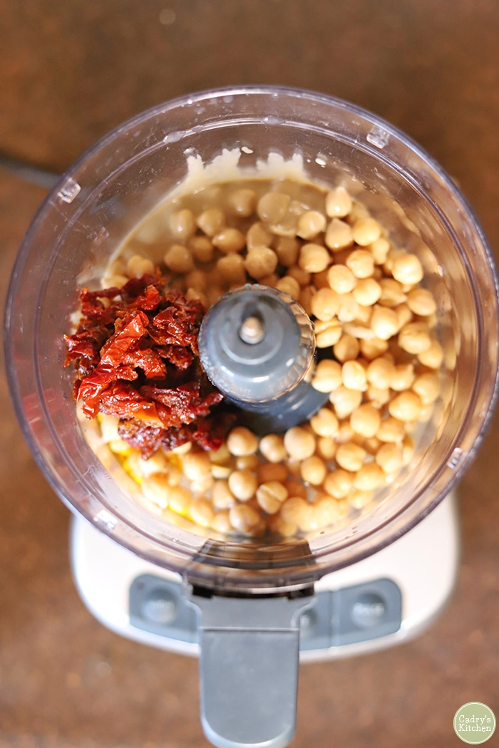Overhead chickpeas, sun-dried tomatoes, tahini, and lemon juice in food processor.