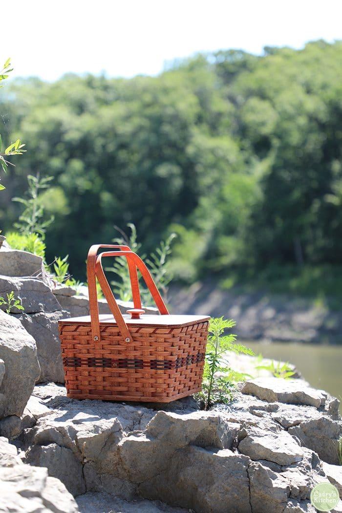 Picnic basket on lake overlook.
