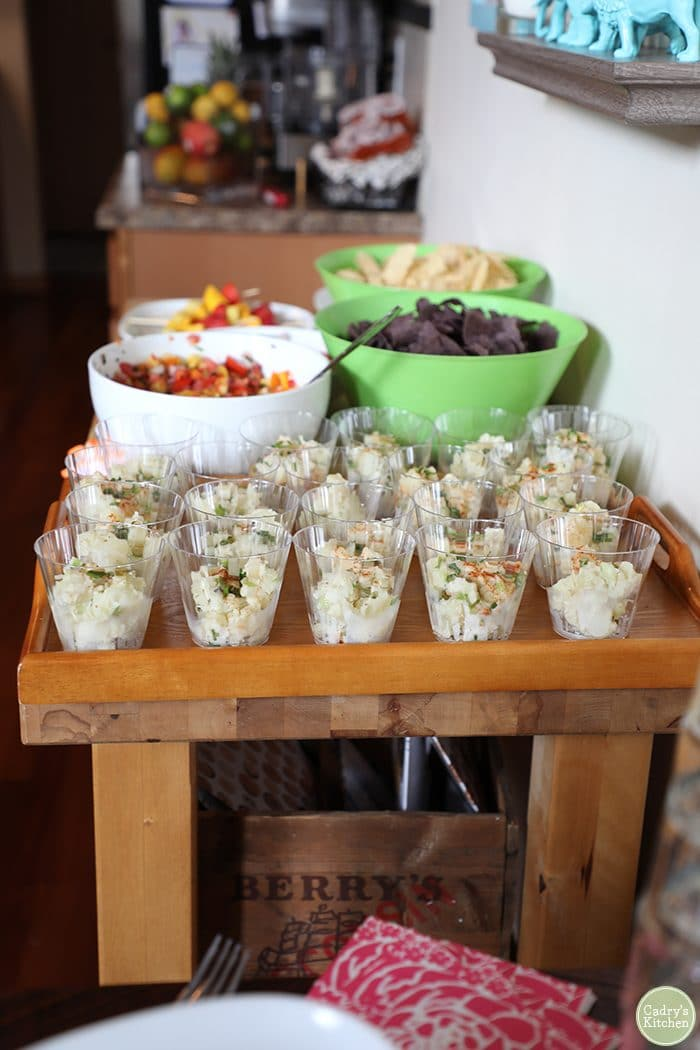 Vegan potato salad in cups for serving, bowls of salsa in background.