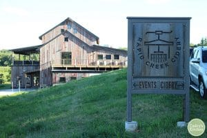Exterior Rapid Creek Cidery in Iowa City on green hill.