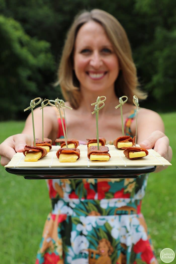 Cadry holding pineapple wrapped in seitan bacon with bamboo skewers. Tiki party ideas.