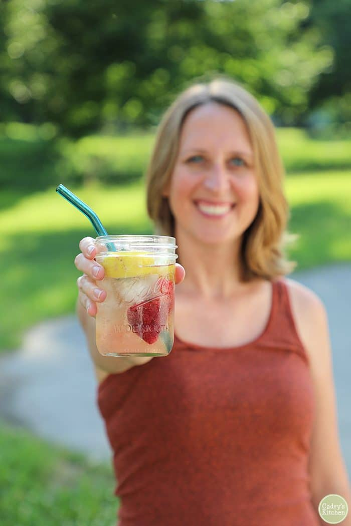 Cadry holding a Ball jar with sparkling strawberry lemonade.
