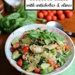 Israeli couscous salad with artichokes and olives in bowl with cherry tomatoes and basil.