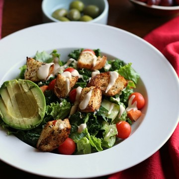Salad with air fryer croutons, avocado, and a drizzle of lemon tahini dressing.