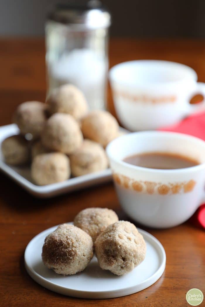 Vegan doughnut holes on a small plate with a coffee cup.