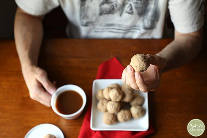 Overhead shot of doughnut holes in a hand with a cup of coffee.