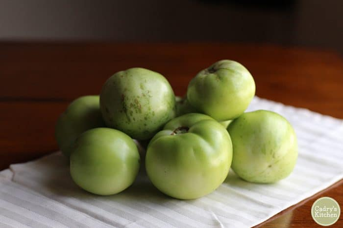 Pile of green tomatoes on a white napkin.