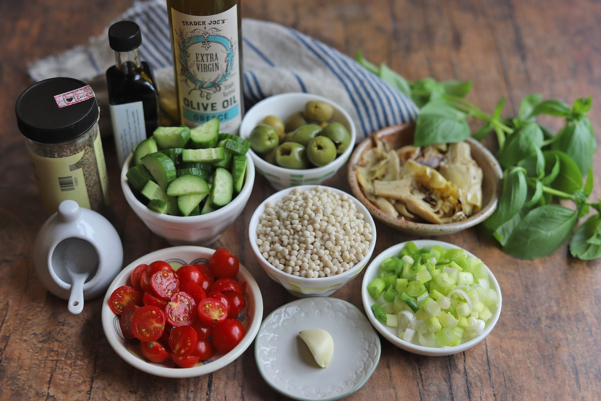Cherry tomatoes, cucumbers, olives, artichoke hearts, dried couscous, garlic, onions, vinegar, salt, and oil on table.