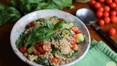 Fresh basil on Israeli couscous salad with cherry tomatoes, Castelvetrano olives, artichoke hearts, and green onion in bowl.