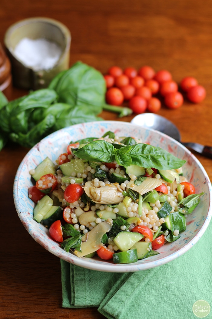 Israeli couscous salad with cucumber, artichoke hearts, tomatoes, and basil in bowl with green napkin.