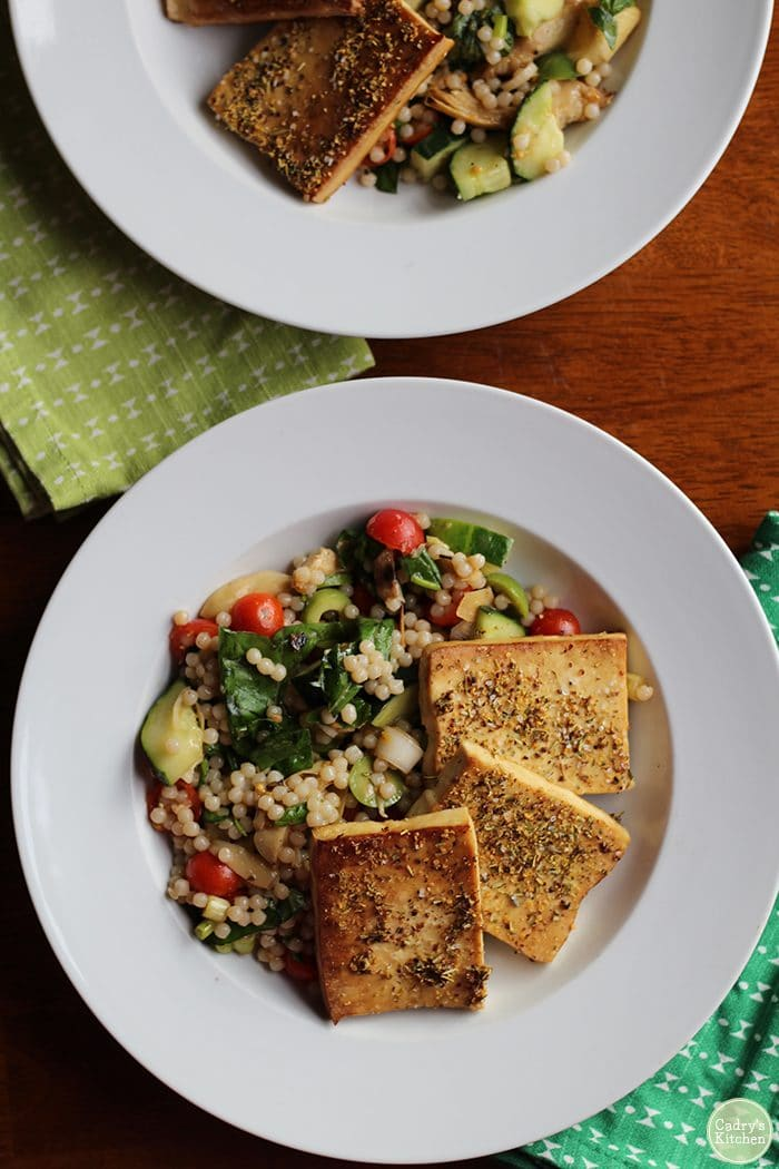 Overhead shot of tofu slabs with Israeli couscous salad in bowl.