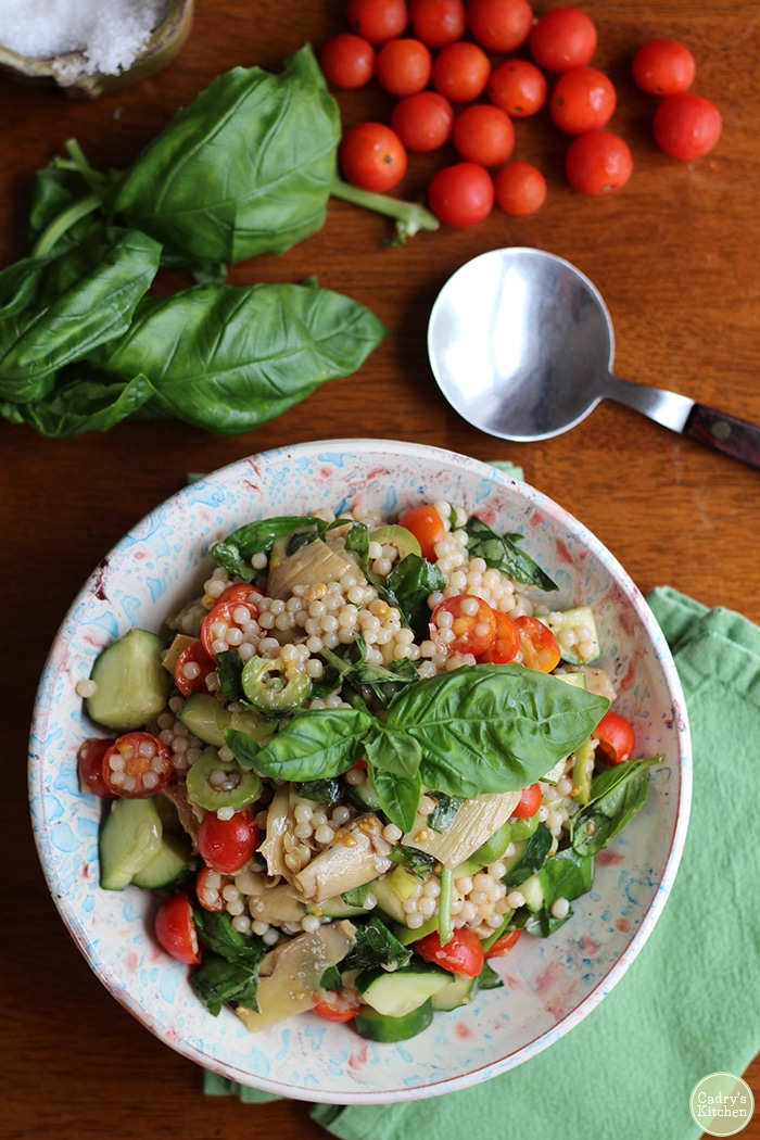 Overhead picture of Israeli couscous with basil, tomatoes, Castelvetrano olives, cucumbers, and artichoke hearts in bowl.