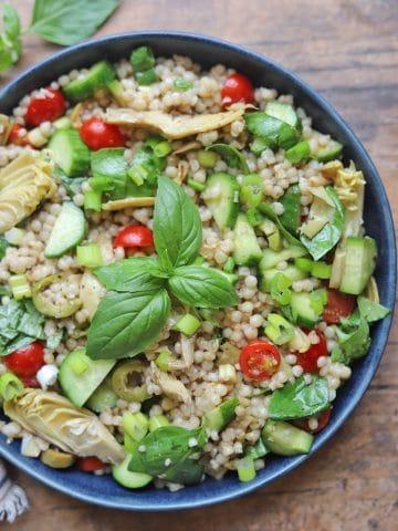 Overhead bowl of Israeli couscous salad on table.