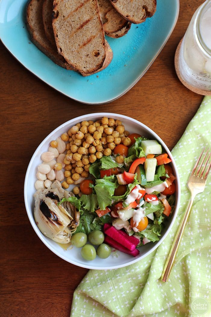 Becoming vegan. Overhead shot salad with chickpeas, roasted artichoke hearts, grilled bread.