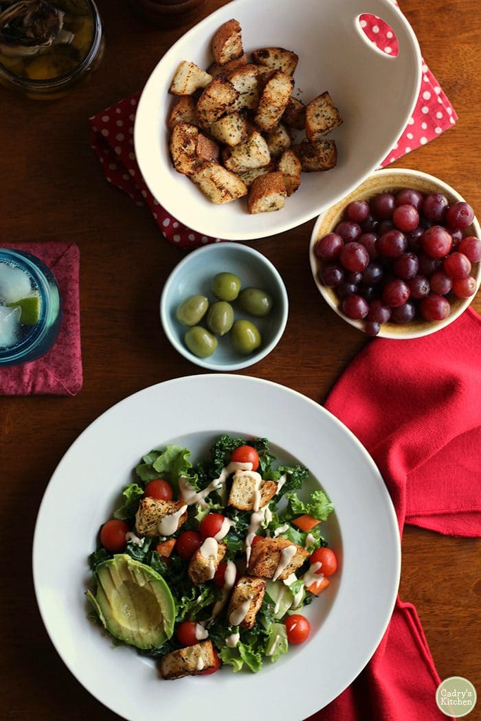 Overhead shot of salad with air fryer croutons, avocado, grapes, and olives.