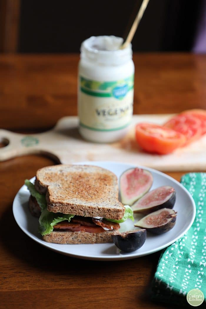 Vegan BLT on plate with Vegenaise in background.