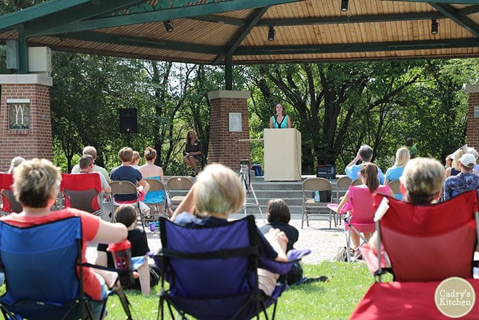 Guests in chairs on grass watching Cadry Nelson speaking on Going Vegan for Good at the Iowa VegFest.