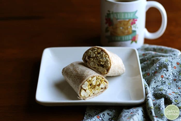 What do vegans eat? Scrambled tofu burrito on square plate with coffee mug.