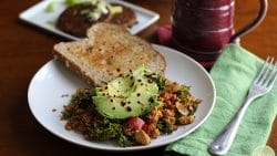 Tofu scramble on white plate with sliced avocado, toast, and veggie sausages.