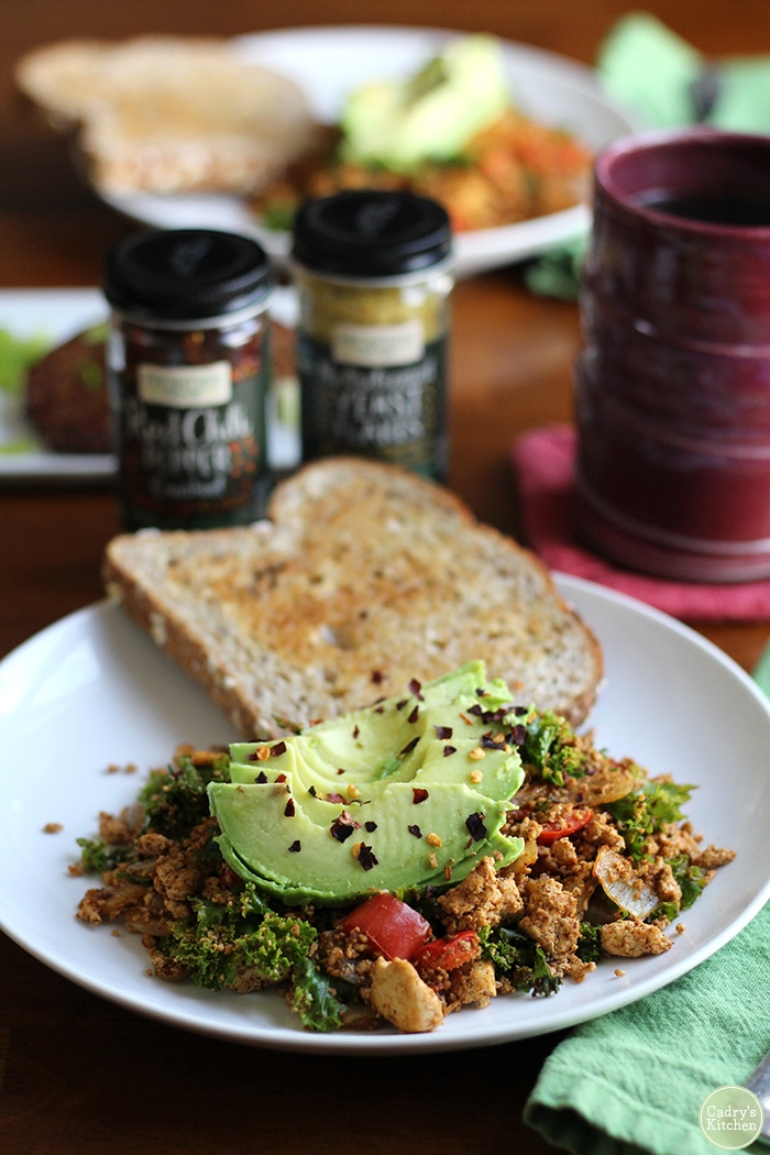 Pile of tofu scramble with sliced avocado and red pepper flakes. Coffee mug in background.