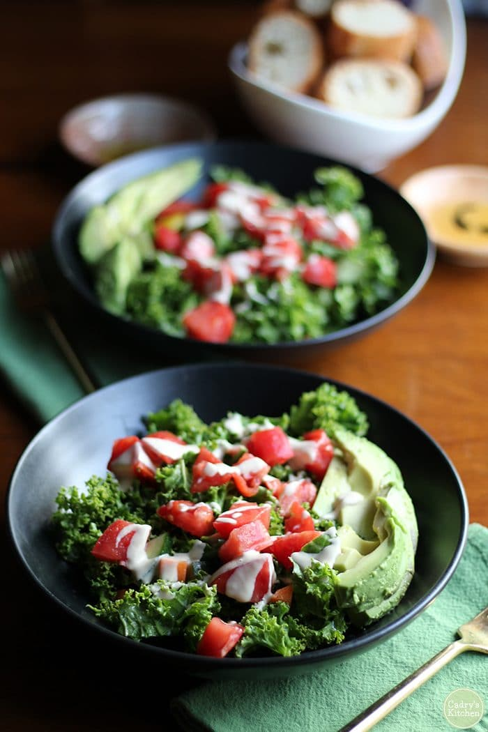 Kale salad in black bowls with avocado. Bread in background.