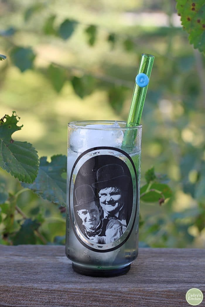 Laurel & Hardy glass with green glass straw on wood surface.