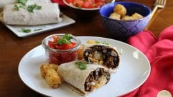 Vegan bean burrito with tater tots and seitan chorizo on a plate with salsa.