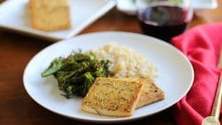 Baked tofu with lemon & rosemary on plate with broccolini & brown rice. Red wine & red napkin on table.