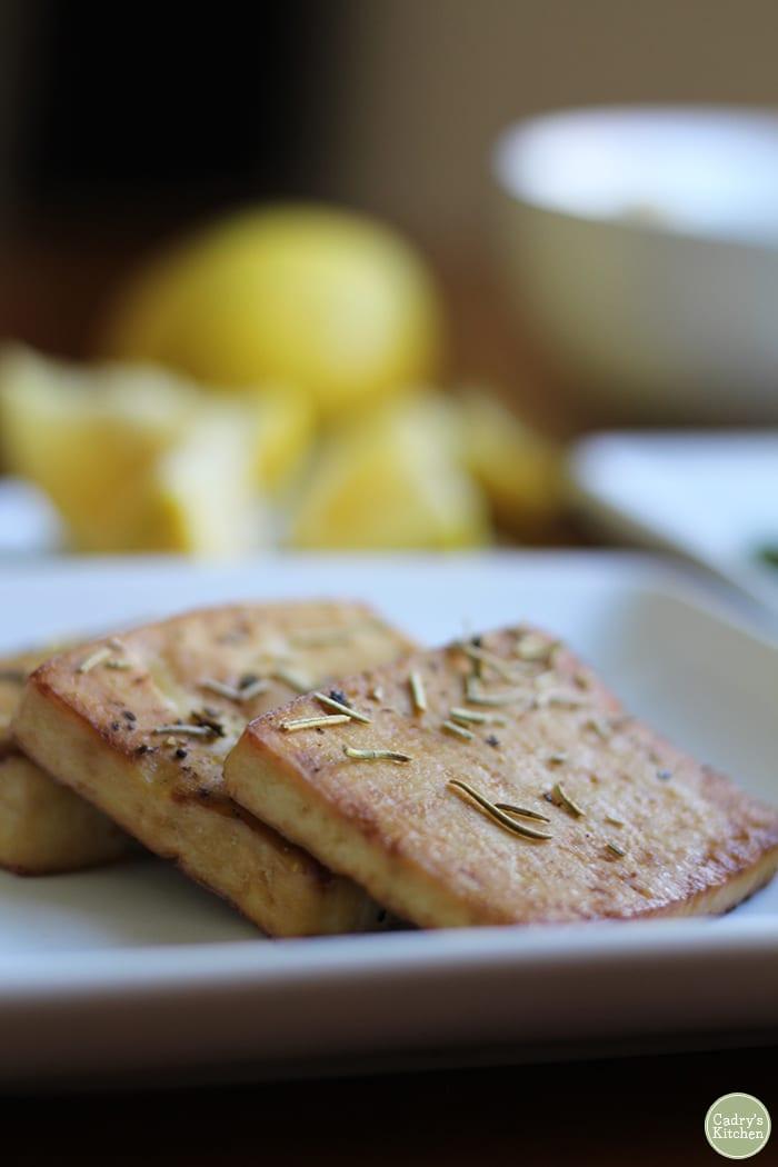 Close-up baked tofu with lemon & rosemary on white plate.