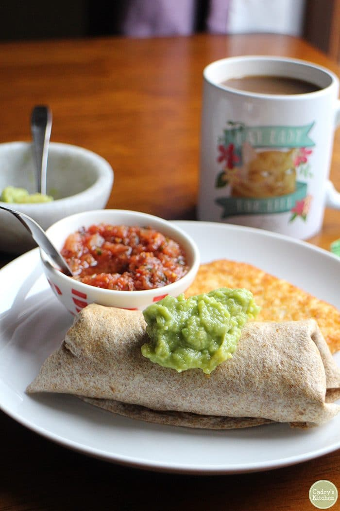 Breakfast burrito with guacamole, salsa, and hash brown patty. Cat coffee mug in background.