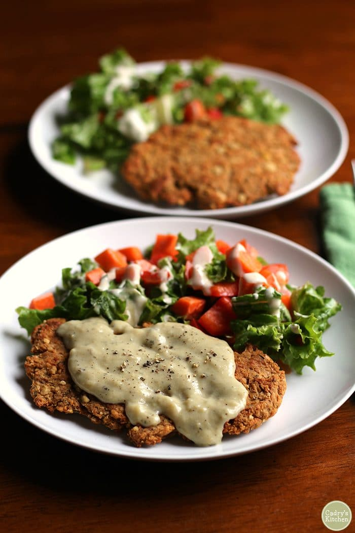 Chickpea cutlet with gravy and salad on white plate.
