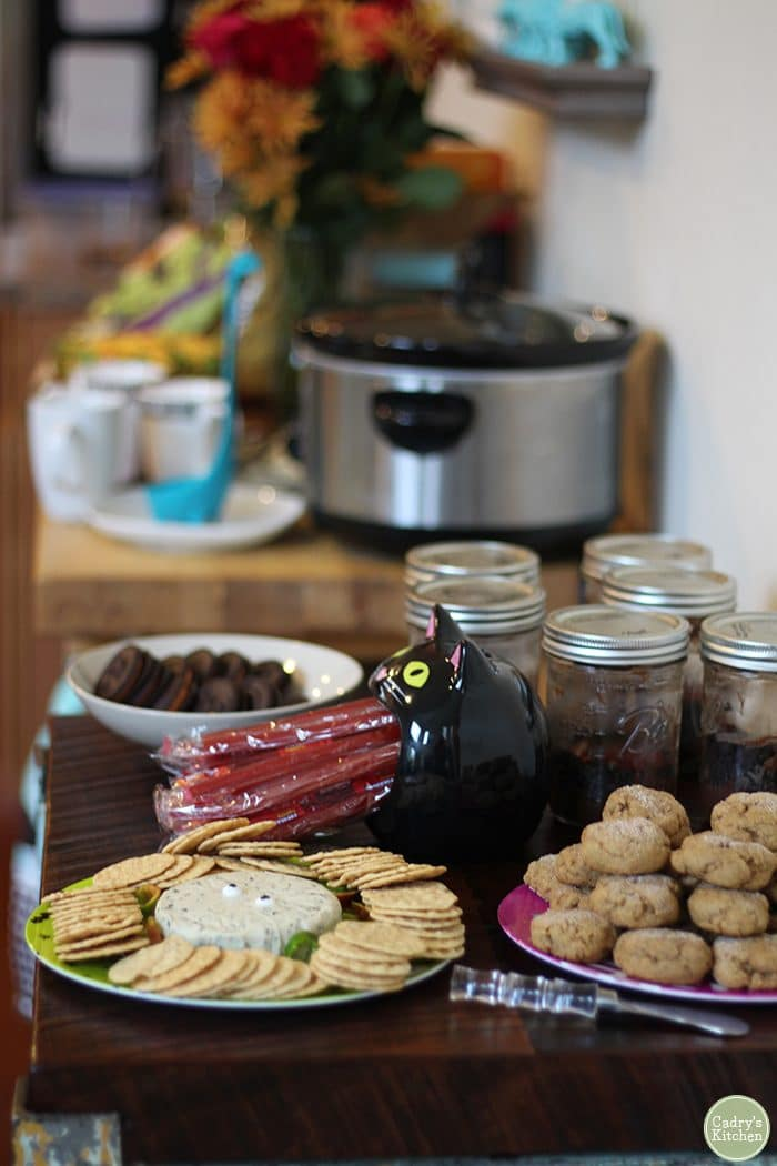 Appetizer table with vegan cheese, cookies, and crockpot.