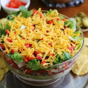 Overhead vegan 7 layer dip in glass bowl with corn tortilla chips.