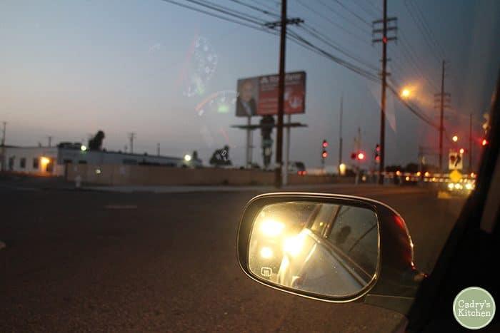 Car mirror, railroad stop at night.