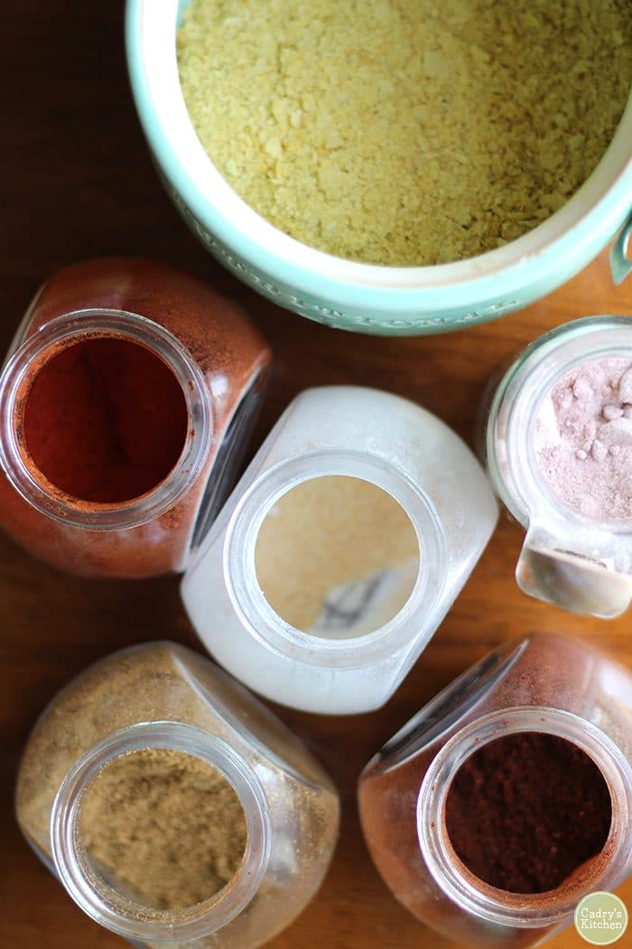 Overhead view jars of spices - cumin, ancho chili powder, onion powder, paprika, kala namak, and nutritional yeast.