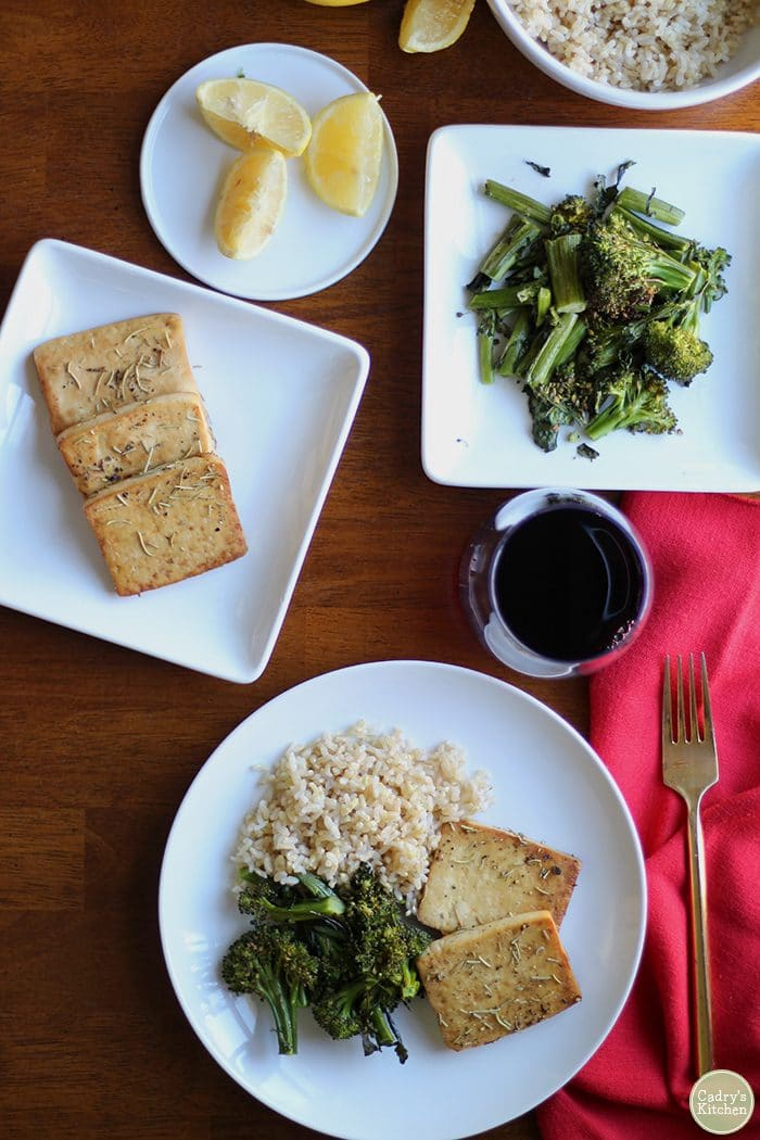 Overhead picture of baked tofu recipe with lemon & rosemary, broccolini, and brown rice.