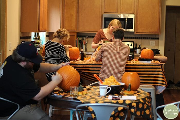 Pumpkin carving party in kitchen.