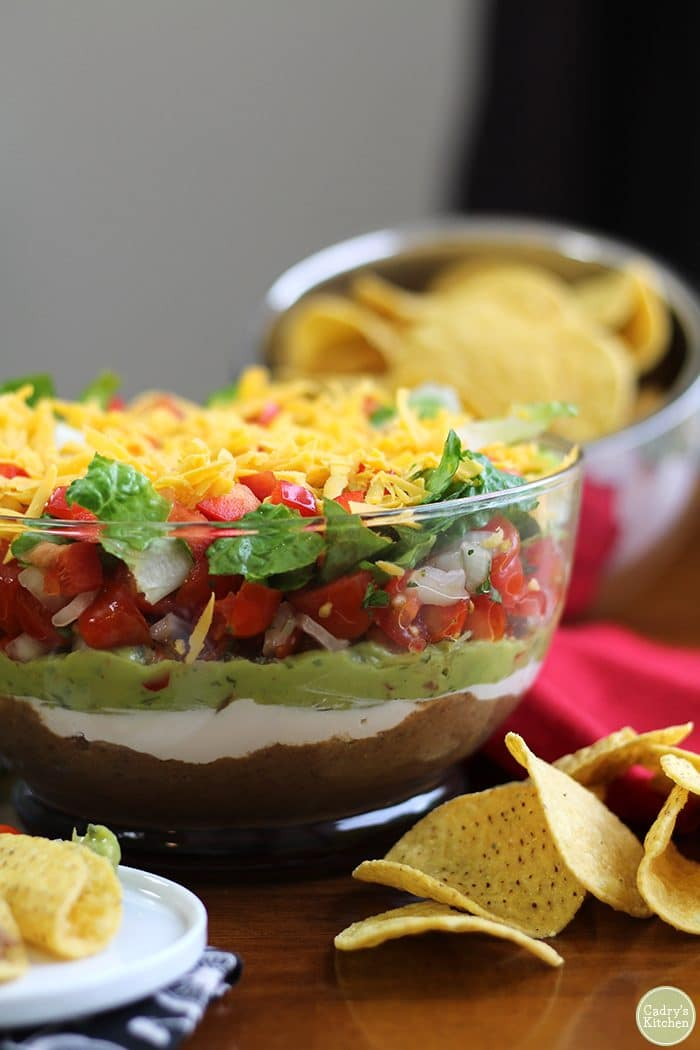 Vegan 7 layer dip in glass bowl with tortilla chips.