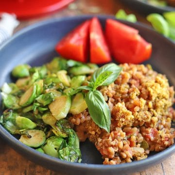 Plate with Brussels sprouts, tomatoes, and baked farro.