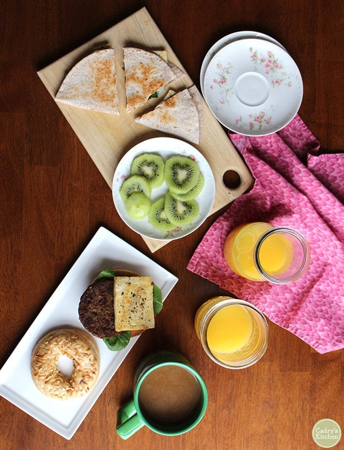 Overhead view of vegan egg with veggie sausage, bagels, kiwi fruit, coffee, and orange juice on table.