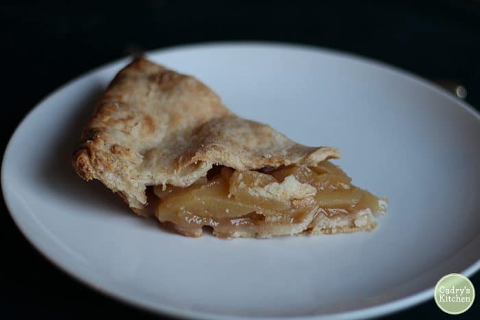 Slice of vegan apple pie on plate.