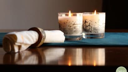 Napkin with napkin ring and two candles on table.