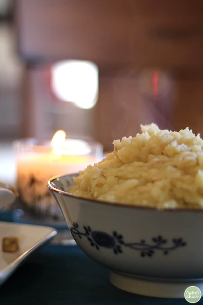 Bowl of mashed potatoes with candle in background.