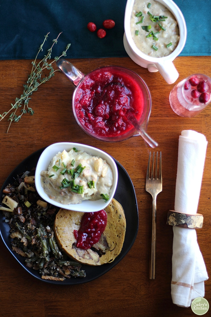 Overhead picture of Christmas dinner side dishes with seitan, mashed potatoes, and cranberry sauce.